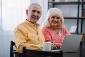 happy retired couple sitting at desk with laptop