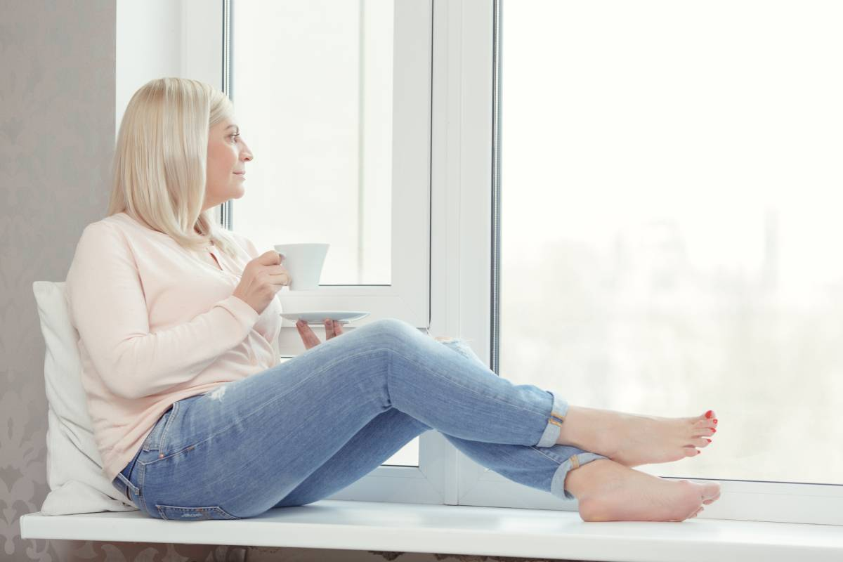 woman sitting in window drinking hot beverage