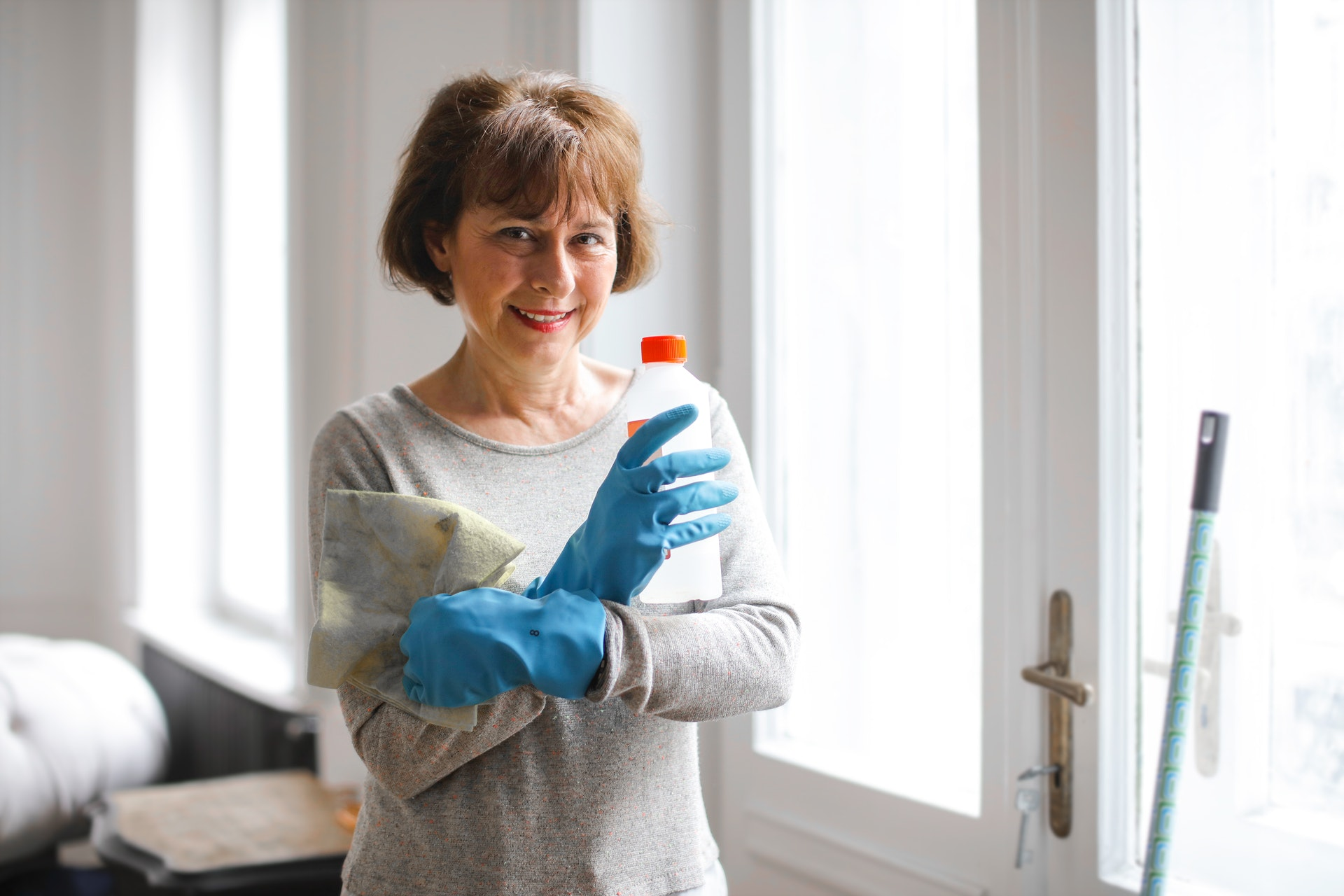 older lady with gloves on cleaning and renovating room