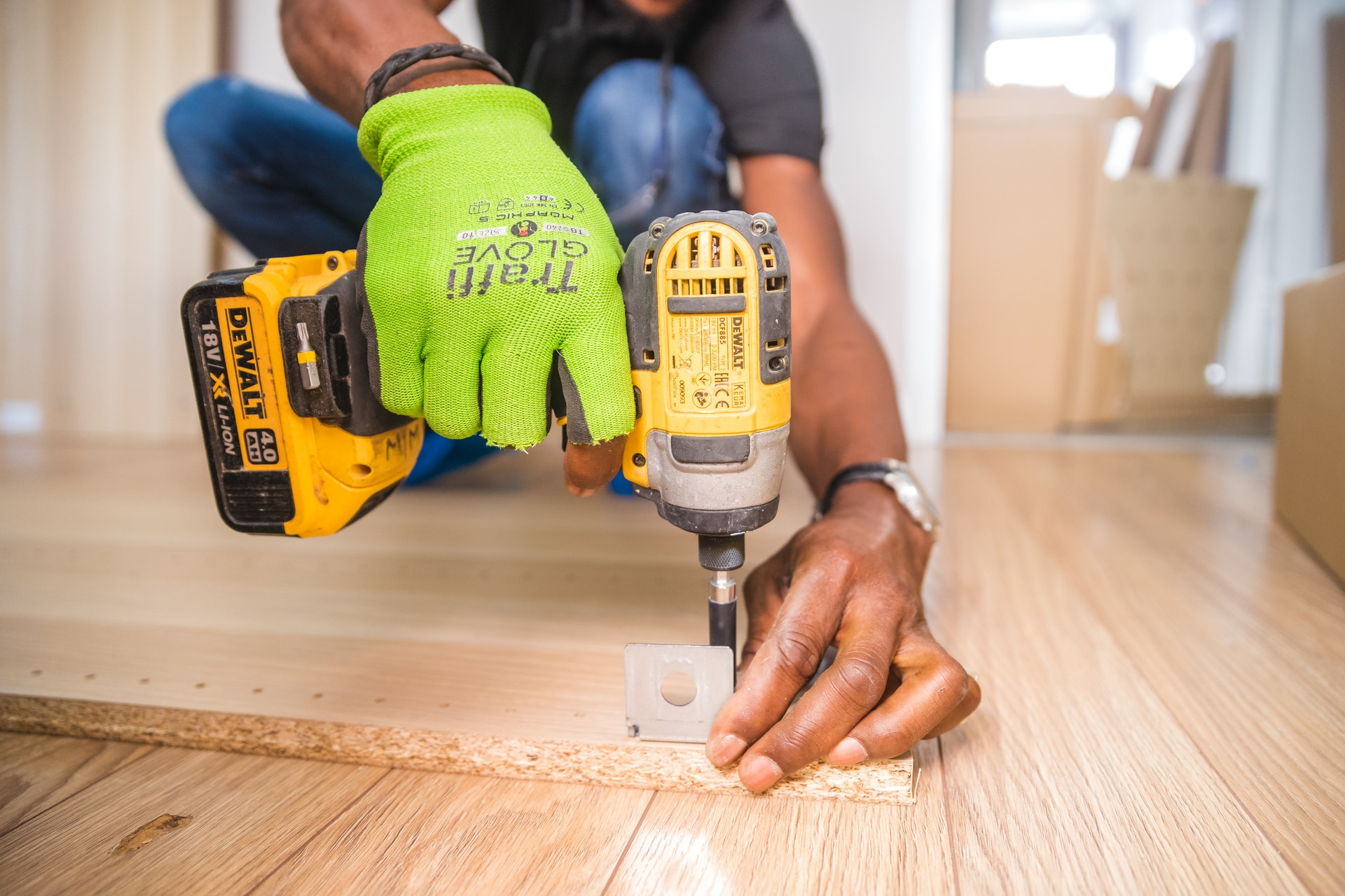man holding drill to wooden floor